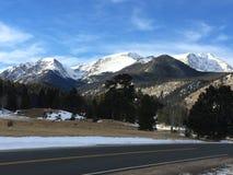As nuvens sobre a neve tamparam picos e estrada de montanha Fotografia de Stock Royalty Free