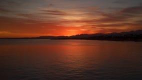 As nuvens sobre o mar pintaram o sol no por do sol video estoque