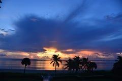 As nuvens sobre o oceano parecem azuis enquanto o nascer do sol começa fotografia de stock royalty free