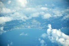 As nuvens veem & cidade de Japão da janela do plano imagem de stock royalty free
