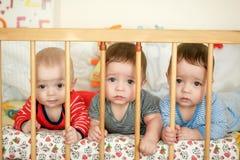 As objetivas triplas recém-nascidas estão encontrando-se na cama Imagem de Stock Royalty Free