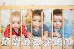 As objetivas triplas recém-nascidas estão na cama Imagem de Stock Royalty Free