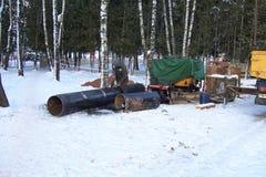 As obras, o trabalhador fazem a limpeza de uma tubulação grande do metal pela ferramenta elétrica para o reparo de um cano princi fotografia de stock royalty free