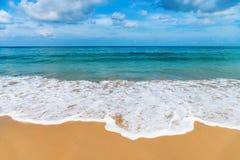 As ondas amáveis pequenas brancas na areia idillic encalham Imagem de Stock