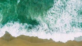 As ondas aproximam a praia Areia amarela e água verde foto de stock