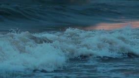 As ondas azuis iluminaram o por do sol alaranjado na luta da praia video estoque