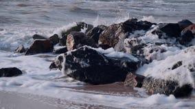 As ondas bateram em um conjunto de pedras pretas no mar na areia contra o céu vídeos de arquivo