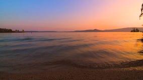 As ondas bateram lentamente contra o Sandy Beach do lago no por do sol bonito video estoque