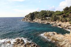 As ondas bateram na costa rochosa, mar Mediterrâneo, casas de campo de beira-mar imagem de stock