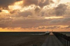 As ondas bateram o cais na frente do por do sol em Nr Vorupoer na costa de Mar do Norte em Dinamarca Foto de Stock Royalty Free