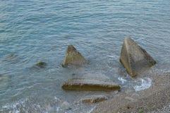 As ondas da batida do mar nos pedregulhos enormes na costa Foto de Stock