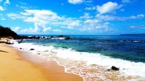As ondas de oceano balançam céus azuis e uma praia bonita fotografia de stock royalty free