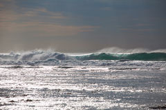 As ondas de oceano fecham-se acima e a faísca da água no por do sol Imagem de Stock Royalty Free