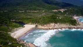 As ondas de oceano rolam no Sandy Beach no lagune entre rochas vídeos de arquivo