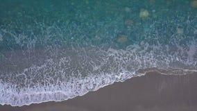 As ondas de turquesa da vista superior quebram em Pebble Beach vazio Mar puro do olho do pássaro filme