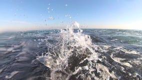 As ondas do mar bateram diretamente na câmera, tiro backlit do mar filme