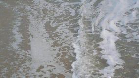 As ondas do mar deixam de funcionar sobre a praia da areia no dia nebuloso filme