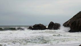 As ondas do moderado que batem promontório das rochas nublam o dia video estoque
