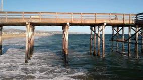 As ondas do verão quebram em uma praia e em um cais mornos de Califórnia video estoque