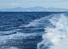 As ondas e a espuma de um barco em um dia de verão brilhante Ilhas e montanhas no fundo Férias de verão fotografia de stock royalty free
