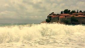As ondas enormes do mar oprimem a costa No fundo é uma ilha magnífica com casas antigas com um telhado telhado vídeos de arquivo