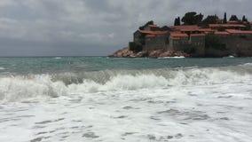 As ondas enormes do mar oprimem a costa No fundo é uma ilha magnífica com casas antigas com um telhado telhado video estoque