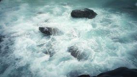 As ondas enormes dramáticas quebram nas pedras litorais vídeos de arquivo
