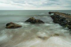 As ondas fluem em torno dos grandes pedregulhos, ao lado de um molhe que alcança para o horizonte distante, a ilha de bloco, RI imagem de stock royalty free