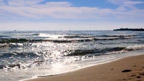 As ondas mediterrâneas da praia na praia no tempo eavning, luz solar refletem na superfície da água Fuengirola, Espanha filme