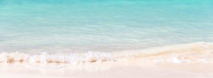 As ondas na areia e na turquesa brancas molham, fundo panorâmico fotografia de stock