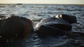 As ondas pequenas deixam de funcionar nas rochas na costa de mar sob a luz do sol ninguém Movimento lento filme