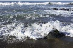 As ondas que esmagam em uma praia rochosa que faz o mar espumam na praia de Moonstone Fotografia de Stock Royalty Free