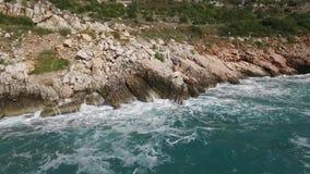 As ondas que quebram em uma praia rochoso, formando um pulverizador footage Espirrar acena nas rochas do mar filme
