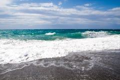 As ondas que quebram na praia abandonada, o fundo SK azul Foto de Stock Royalty Free