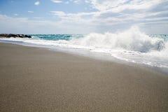 As ondas que quebram na praia abandonada, o fundo SK azul Imagens de Stock Royalty Free