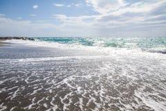 As ondas que quebram na praia abandonada, o fundo SK azul Imagem de Stock Royalty Free