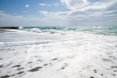 As ondas que quebram na praia abandonada, o fundo SK azul Fotografia de Stock