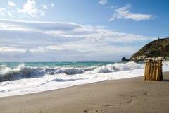 As ondas que quebram na praia abandonada, o fundo SK azul Imagens de Stock