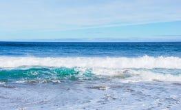 As ondas que rolam para a praia, o azul perfeito e o oceano do aqua molham, nuvens de altostratus no céu Fotografia de Stock
