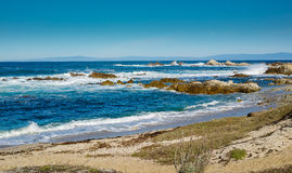 As ondas quebram na angra e no Sandy Beach rochosos sob o céu azul Imagens de Stock