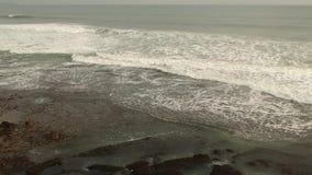 As ondas a?reas da vista superior quebram em rochas escuras perto da praia E filme