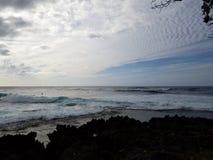 As ondas rolam na costa com as nuvens no céu Fotos de Stock