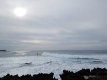 As ondas rolam na costa com os povos que surfam Fotografia de Stock Royalty Free