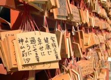As orações japonesas escritas em partes de madeira penduram em um templo Fotografia de Stock
