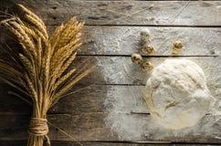 As orelhas do trigo amassaram ovos da massa e de codorniz em uma tabela de madeira Imagem de Stock