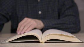 As páginas da consultação da pessoa do livro velho, as testas masculinas da mão registram páginas video estoque