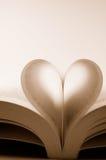 As páginas de um livro curvaram-se em uma forma do coração Imagens de Stock