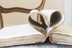 As páginas do livro aberto rolaram na forma do coração Imagem de Stock