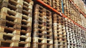 As páletes de madeira para a distribuição e o transporte de produto são empilhadas na cremalheira do armazém Imagens de Stock Royalty Free