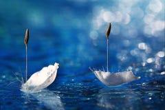 As pétalas na água gostam da cisne dois na lagoa imagens de stock royalty free